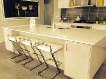 Huge Stone Worktop Incorporates Breakfast Bar Plus Full Depth Cupboards Instead Of Shelves To