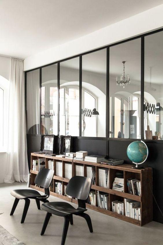 Un coin lecture avec une bibliothèque en bois brut vieilli, des assises noires élégantes et un sol en béton ciré