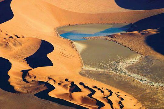 L'Erg du Namib en Namibie Ce site exceptionnel qui s'étend sur plus de 3 millions d'hectares est le seul désert côtier où l'on trouve d'aussi vastes champs de dunes de sable sous l'influence du brouillard. L'endroit est particulièrement intéressant car les dunes y sont constituées de matériaux venus de très loin, transportés depuis l'intérieur de l'Afrique australe par les cours d'eau, les courants océaniques et le vent.
