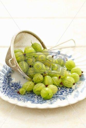 Fresh gooseberries in a sieve on plate
