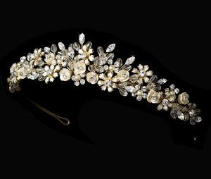 """Acalia Gold Champagne Porcelain Flower Accented Wedding Bridal Tiara by Fairytale Bridal Tiara. Save 32 Off!. $68.45. Porcelain Flowers. Freshwater Pearls. Rhinestones. Swarovski Crystals. Size: The ornamented portion of the piece measures 8-3/4"""" wide and 1"""" tall. Classic and elegant, this gold plated tiara features a bridal bouquet of rum pink porcelain flowers, freshwater pearls, golden flower details, rhinestones, and a spray of clear Swarovski crystals. A beautiful acces..."""