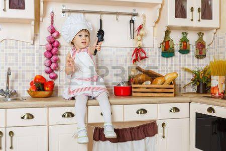 Kleines Mädchen in der Schürze und Kappe der Koch sitzt in der Küche im Haus. Mutter Helfer. 2 Jahre alt. Lizenzfreie Bilder