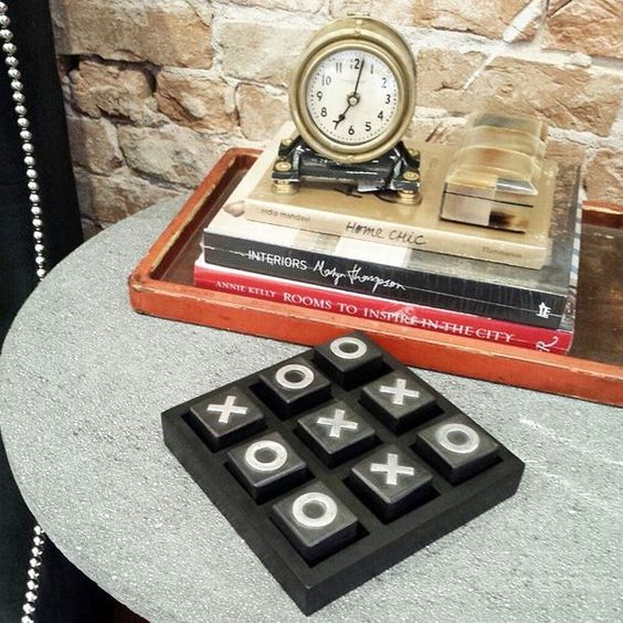 This wood + metal table top tic-tac-toe is perfect for a coffee table! Let the games begin! #designlabddg #xoxo #tictactoe #3inarow #zinctable #books #clock
