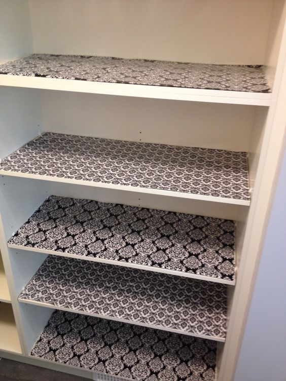 My new pantry shelves lined with wrapping paper from Michaels ($1.50 per roll) covered in clear adhesive shelf liner from the Dollar store.