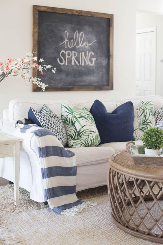This spring interior is simple using white as a base colour but incorporates several trends. The subtle peach from the flowers, and the snorkel blue tie in with Pantone's colours of the year. The palm tree pillows add a pop of colour to the room and add the 'jungle' trend of this season.