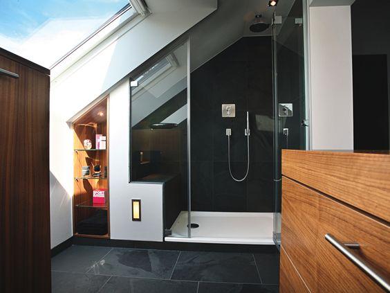 Gegenüber der Eckbadewanne an der zweiten Schmalseite wurde die geräumige Duschkabine untergebracht. Ein gemauerter und gefliester Sockel bietet eine Sitzgelegenheit. In die Schräge konnte auch ein Regal integriert werden.