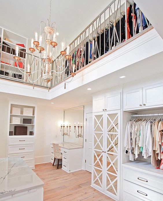 Two story walk-in closet with a chandelier @easleybuilders: