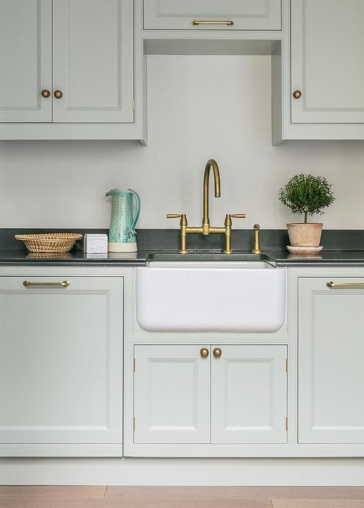 A Small Farmhouse Sink With Antique Brass Deck Mount Gooseneck
