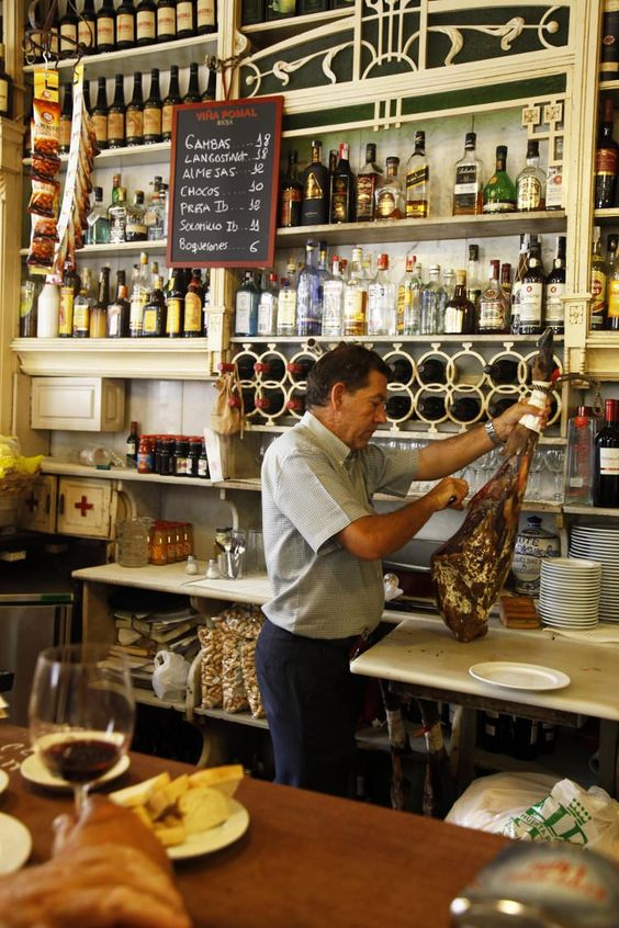El Rinconcillo, Seville's oldest tapas bar, man carving cured meat, Seville, Andalucia: