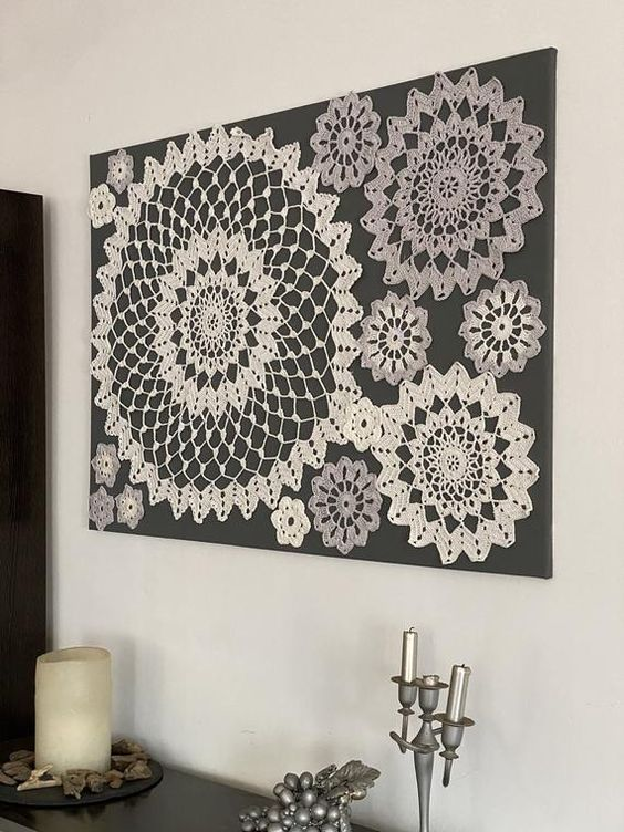Cuadro hecho a ganchillo sobre lienzo gris oscuro , con aplicaciones en blanco y gris claro