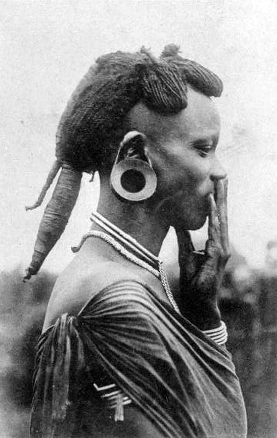 Africa | Woman with elaborate hairstyle and large ear plug. Kenya; ca. 1920- 1940 || Scanned photographic postcard.