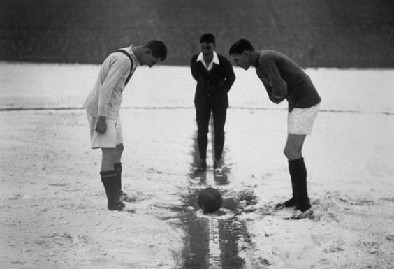 January 1926: The players and referee shiver on a snow-covered pitch at the start of the match between Arsenal and Manchester United. @Gavin Bernard @Ben Helfen