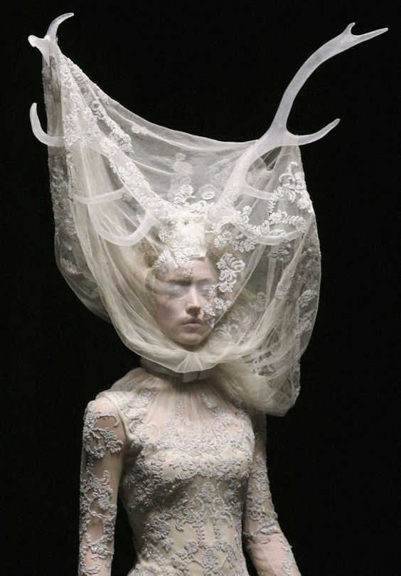 Alexander McQueen. embroidery makes parts of the sheer fabric headress opaque. beautiful and intricate.