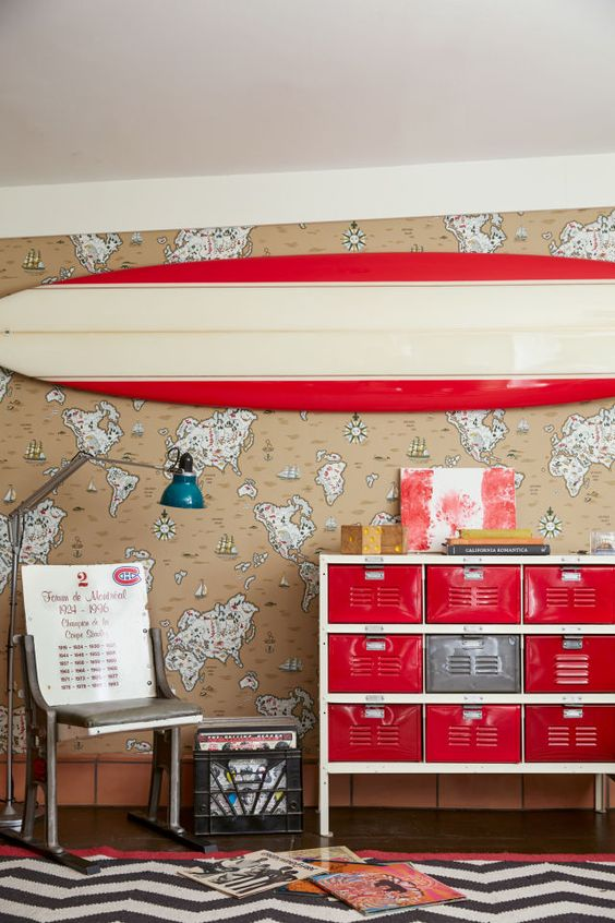 This converted garage man cave features ruby-red accents and nautical map wall paper that's neutral but definitely not boring.