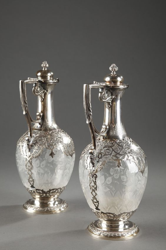 A late 19th century pair of crystal ewers with silver frame, the paunch finely engraved with bunches of flowers and foliated branches. The collar and base are richly decorated with...