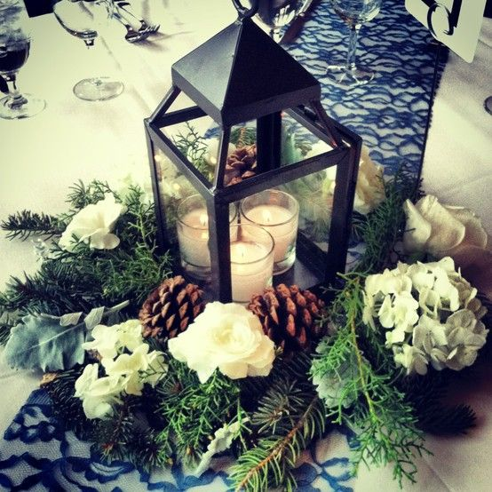 Lanterns surrounded by greens, white flowers and pine cones.  One of three kinds of centerpieces we used at a wedding at the Grand Hall at Copper Station in Copper Mountain, Colorado.:
