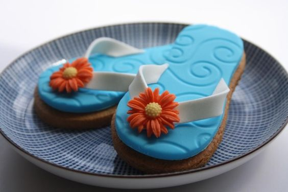 These are some very cute flip flop cookies I made using blue embossed sugar paste with orange and yellow daisies. The design was copied from a fab Lindy Smith book.