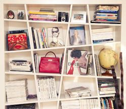 White shelves display books as objects, and other objects