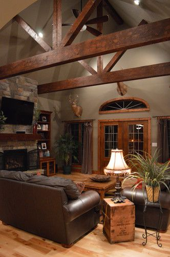 Exposed dark wood beams and stone fireplace... Yes Please! Love except for the TV mounted above the fireplace, why do people do that it ruins it!?