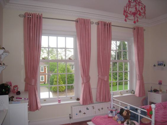 Pink eyeletted curtain installation for a children's room.