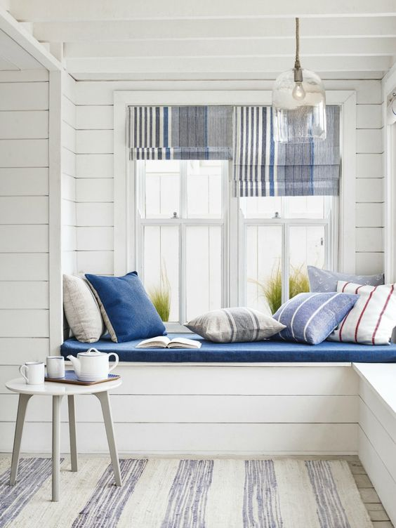 A bright and airy window seat in a beach house living room. Nautical never looked so good.