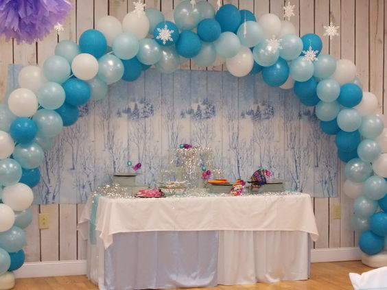 Candy table with winter backdrop and balloon arch over snow