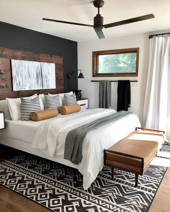 rustic inspired bedroom design // black and white tribal print rug // leather bench // reclaimed wood headboard // modern ceiling fan