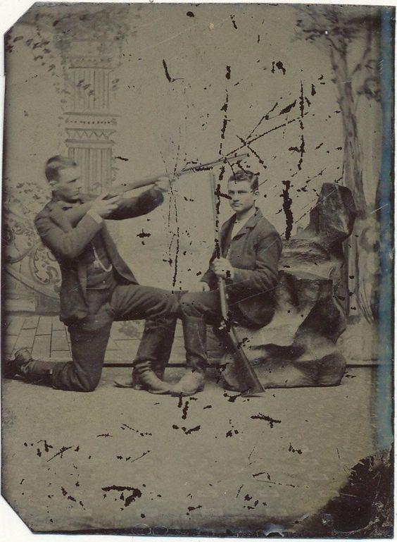 Two men posing with guns