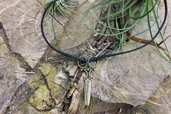 Joli collier ciseaux fais main, de couleur bronze, garnit avec une petite perle en pâte polymère verte brillante. Accrochée d'un cordon en suédine noir 3mm et d'un fil en nylon tressé 1mm vert mesurant 40cm de longueur, on l'attache à l'aide d'un mousqueton. Son tour de cou peu aller de 20 à 22.5cm. La longueur du ciseau est de 6cm.