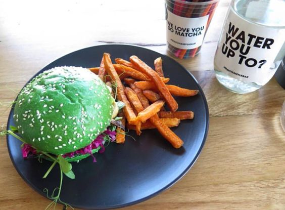 """Droolworthy snap of our """"chicken"""" burger and sweet potato fries from @nutritionlove_ - one of our favourite things on the menu. """"Just found my new favourite place in @aclandvillage - All plant based Matcha Mylkbar  Today I had the soy burger filled with avocado beetroot inside a match bun  YUM"""" by matcha_mylkbar"""