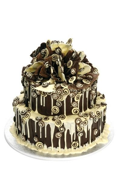 enrobed in dark Belgian chocolate coating with a white run over, finished with handmade, delicious swirly funky, two tier cake .. buttons of mixed chocolate and topped with an explosion of chocolate ruffles
