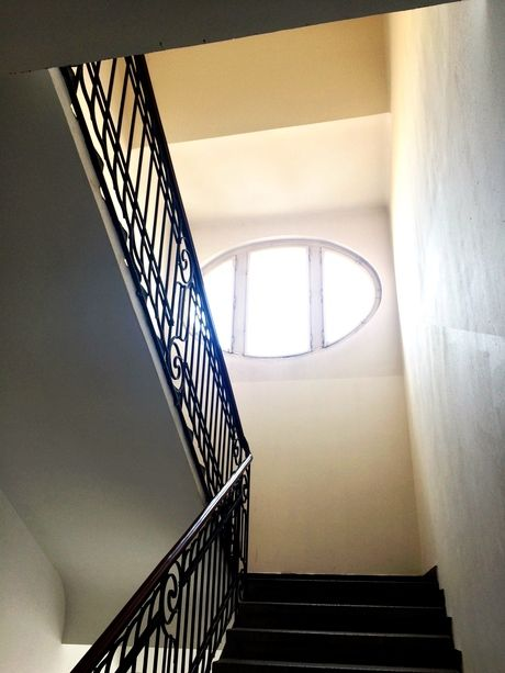 an apartment staircase and an oval window in Prague. Classical.
