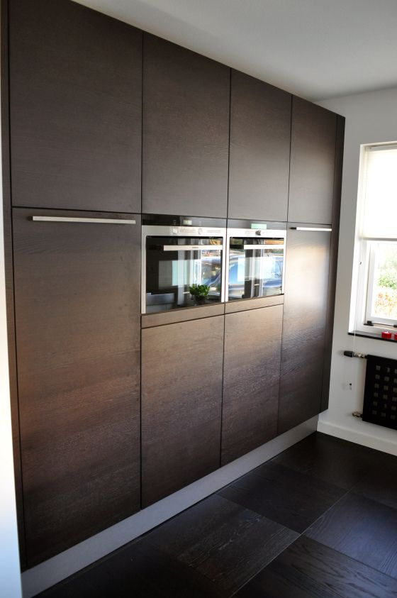 Donker grijze keuken met rode krukken aan het kookeiland ...