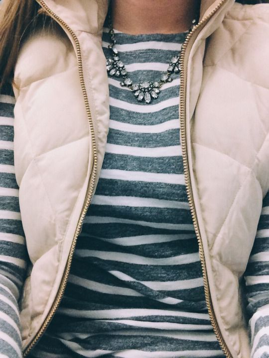 Gray and white striped shirt, cream-colored vest, and statement necklace.