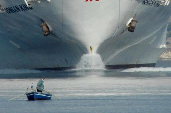 STRANGE SEASIDE DANGERS - OLD MAN IN A ROW BOAT LOOKS BEHIND HIM - HUGE SHIP HEADING RIGHT AT HIM!