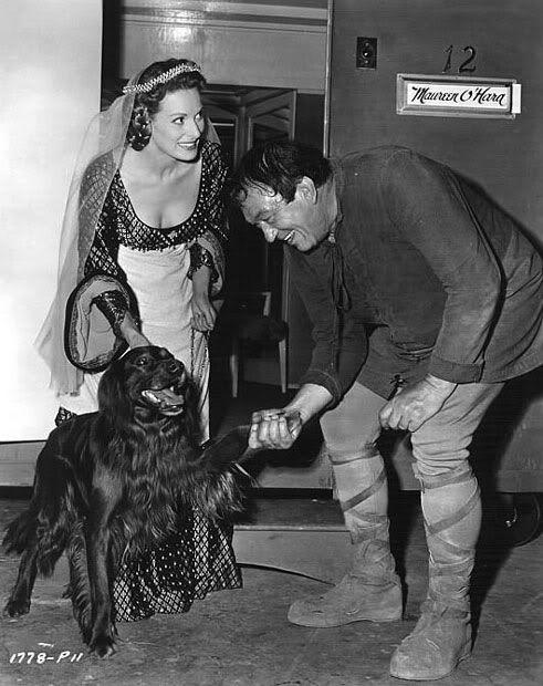 "Maureen O'Hara's Irish Setter Pogo greets Victor McLaglen   on the set of ""Lady Godiva"""