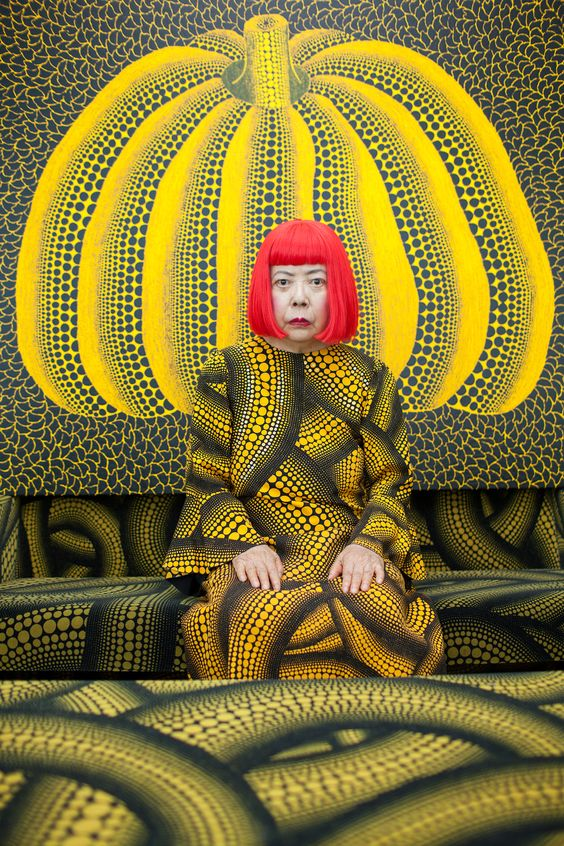 Portrait of Yayoi Kusama in costume in front of pumpkin painting