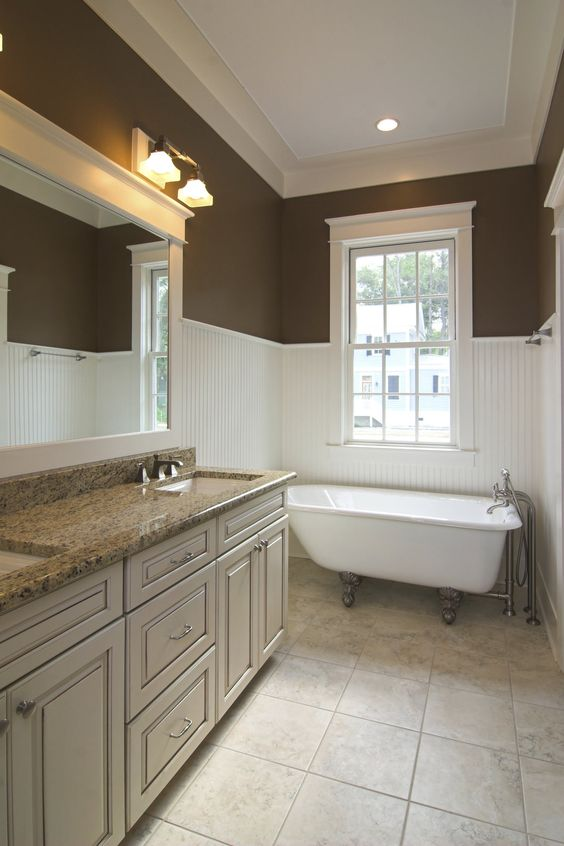 Updated bathroom with traditional wainscoting extending fairly high up the wall.
