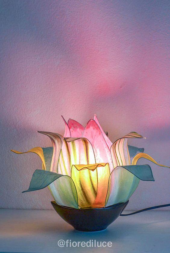 Fiore riflesso nell'acqua Una lampada dalle foglie tenere riflette il rosa dei suoi petali centrali, giochi di luce che intrecciano i toni del giallo, del verde e del rosa, come un fiore che esce da una fiaba creerà un ambiente di serenità e pace. Composto da petali centrali