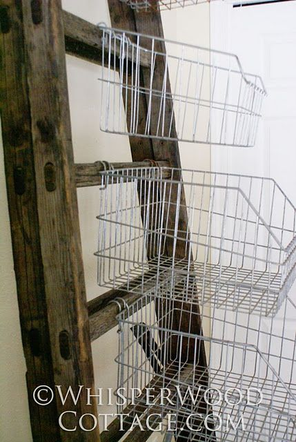 Vertical storage with vintage wire baskets and an antique ladder.