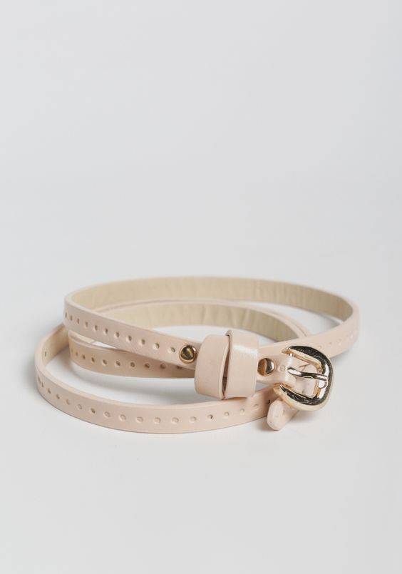 Crafted in a darling light pink hue, this faux leather belt is perfected with gold-toned hardware and circular imprints all around.