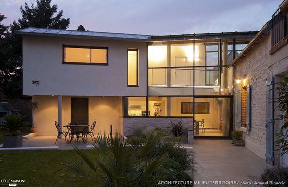 Un maison avec une grande baie vitrée qui laisse entrer la lumière.