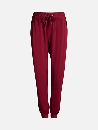Comfortable loose fitting pants with wide elastic drawstring waistline and ribbed bottom hem. Side pockets. Röd
