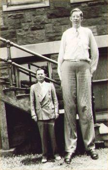 """Робърт Вадлоу, най-високият човек, който някога е живял, заедно с баща си.  Робърт Вадлоу беше 8'11 """", а баща му беше 5'11"""".  Тази снимка е интересна, защото се случва оптична илюзия.  Тъй като баща му стои по-ниско от Робърт, той прави Робърт да изглежда дори по-висок.  Обикновено се изкачваше малко над кръста на Робърт.  Той трагично умира на 22-годишна възраст от инфекция, причинена от блистер на крака му."""