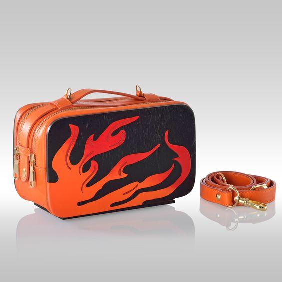 Mini Bag Flame by Francesca Torsi  Minibag in legno nero e pelle arancio con manico e tracolla. Traforo in legno arancio e rosso. Dotata di portacellulare e gancio portachiavi interni. Doppio scomparto con chiusura a zip e dettagli in oro. Una piccola opera d'arte per chi vuole stupire.
