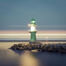 A brilliant long exposure technique: the lines in the back of the photo are a ship passing behind the lighthouse
