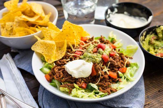 Recept voor mexicaanse gehaktschotel voor 4 personen. Met zout, olijfolie, peper, gehakt, ijsbergsla, cherrytomaat, komkommer, avocado, tortillachips, knoflook, limoen, paprika en yoghurt