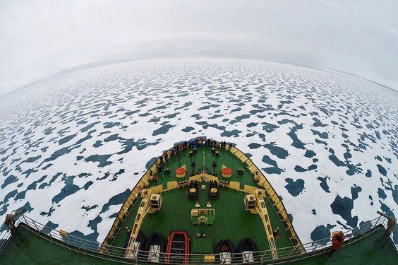 A ship sails through icy waters in the Arctic Ocean