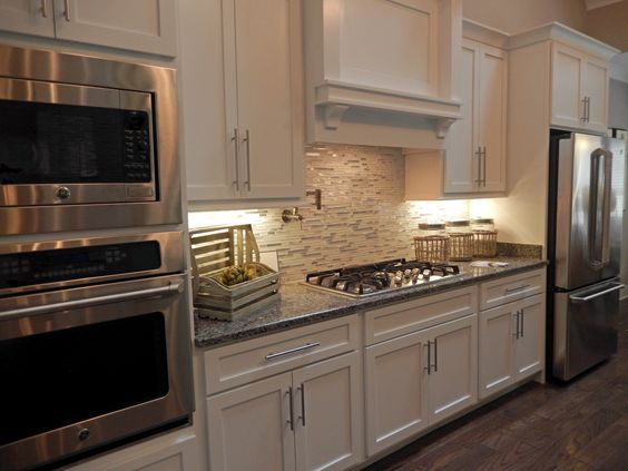 White Kitchen Cabinets. Gray Granite Countertops. New Caledonia Granite from Granite Warehouse. GE Cafe Appliances. White glass and metal Backsplash from Louisville Tile.