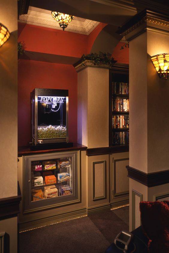 This custom home theater was architecturally designed by Jordan Rosenberg and Associates and features custom lights, popcorn machine, candy inlay and movie shelve